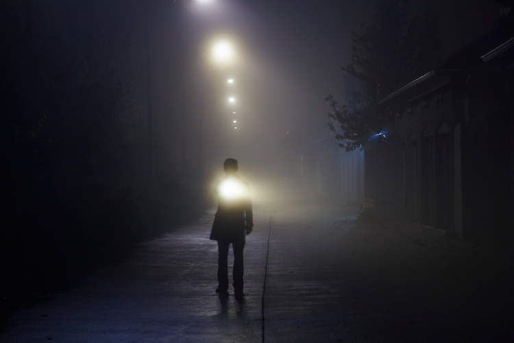 Man searching with flashlight in an alley on a foggy night.