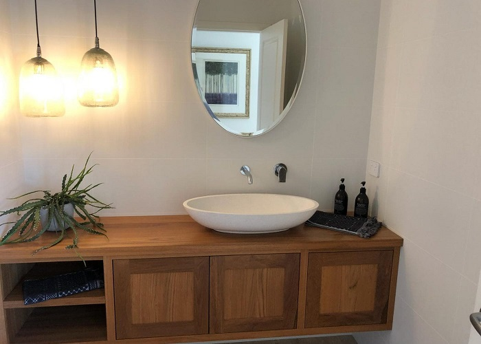picture of modern bathroom with wooden basinet and white sink, with mirror and lights
