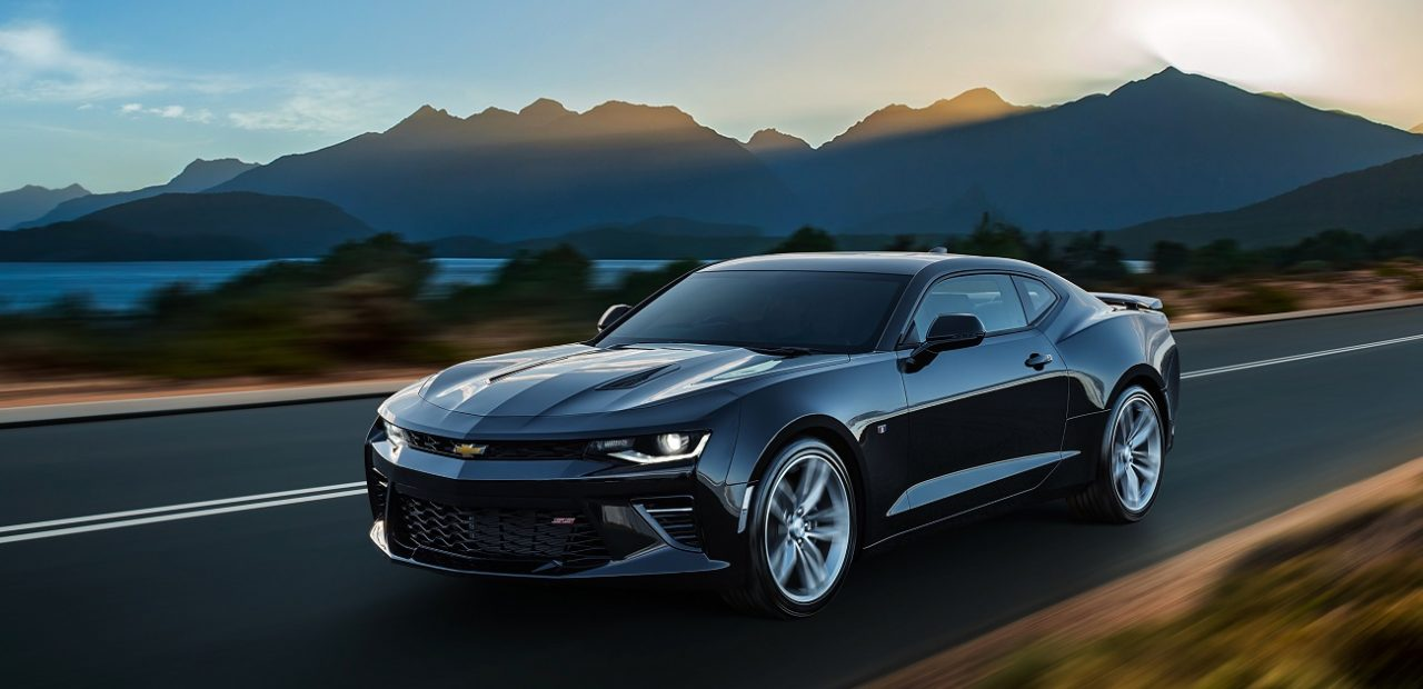picture of a new car driving beside a lake and mountains