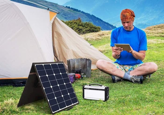 man camping on the mountain and sitting near portable foldable solar panels
