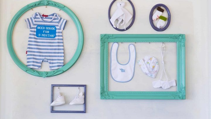 picture of baby's stuff in a blue frames on the wall
