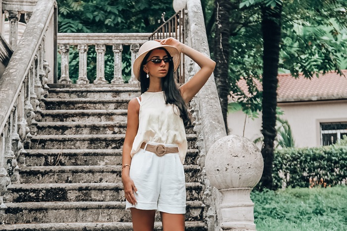 picture of a girl on an outdoor stairs of a house wearing white summer outfit with accessories