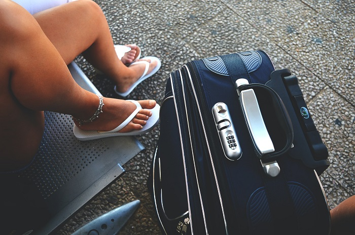 picture of women in flip flop beside a travel bag