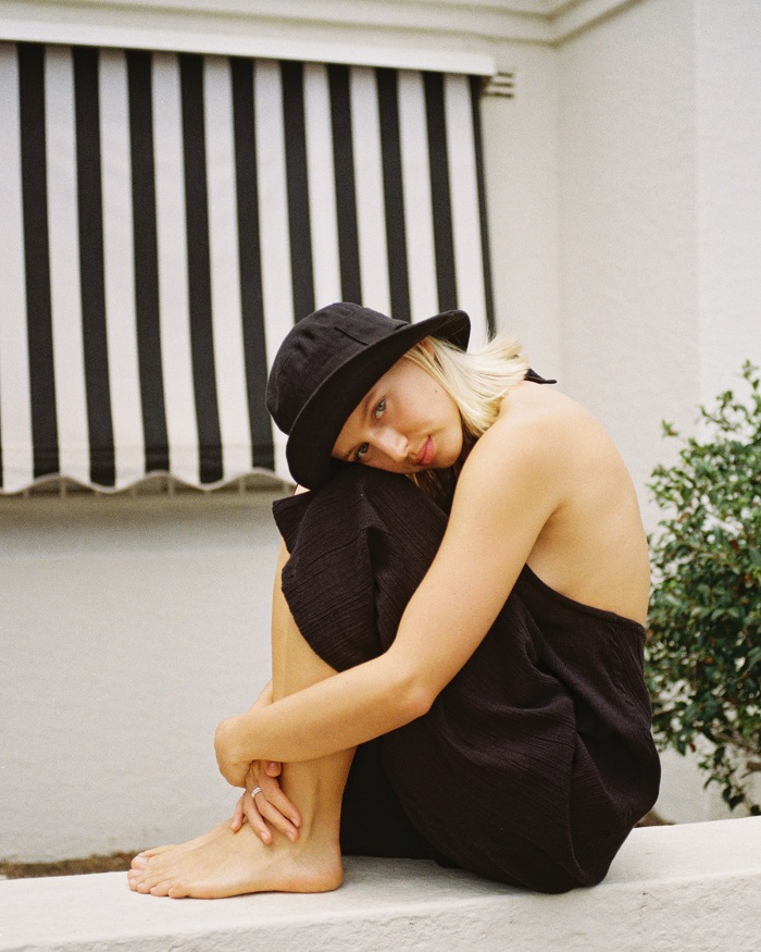 picture of a woman sitting on a concrete wearing black outfit and bucket hat